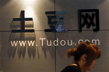 A pedestrian walks past the company logo of Tudou located at their headquarters in Shanghai August 17, 2011. REUTERS/Aly Song