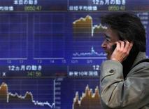 Мужчина проходит мимо электронного табло фондовой биржи в Токио, 12 декабря 2011 г. Фондовые рынки Азии выросли в пятницу после сигналов об усилении экономического восстановления в США. REUTERS/Toru Hanai
