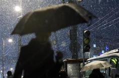 Пешеходы идут под сильным снегопадом в центре Москвы, 8 ноября 2011 г. Наступающие выходные в Москве будут хмурыми и дождливыми, ожидают синоптики. REUTERS/Reuters Staff