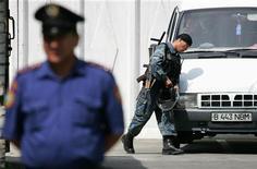 Вооруженный сотруднки полиции у здания суда в Талдыкоргане, в 250 километрах к северу от Алма-Аты 14 июня 2006 года. Уличные выступления уволенных нефтяников на западе Казахстана омрачили в пятницу празднование дня независимости страны, сообщили власти. Пользователи интернета столкнулись с перебоями в доступе к социальным сетям, транслировавшим информацию о беспорядках. REUTERS/Shamil Zhumatov