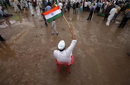 A supporter of social activist Anna Hazare waves the national flag at Ramlila grounds in New Delhi August 23, 2011. REUTERS/Adnan Abidi/Files