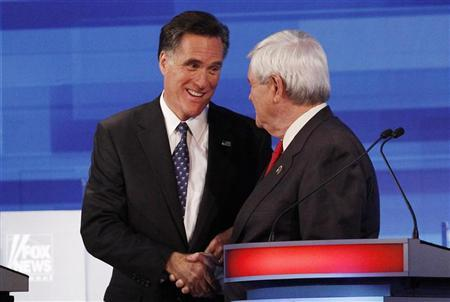Republican presidential candidates, former Massachusetts Governor Mitt Romney (L) and former Speaker of the House Newt Gingrich (R-GA), shake hands at the conclusion of the Republican Party presidential candidates debate in Sioux City, Iowa, December 15, 2011. REUTERS/Jim Young