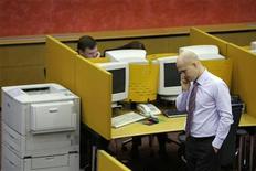 Трейдер говорит по телефону в зале биржи ММВБ в Москве, 16 октября 2008 года. Российский фондовый рынок завершает неделю снижением при заметно упавшей активности участников торгов, которые предпочитают наблюдать за движением котировок с закрытыми позициями.   REUTERS/Denis Sinyakov  (RUSSIA)