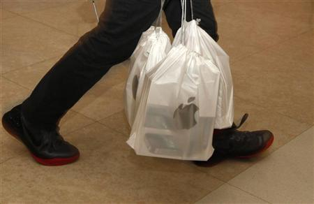 A man carries packs of Apple iPhone 4S, with each pack containing five sets, outside an Apple store in Hong Kong November 11, 2011.  REUTERS/Bobby Yip