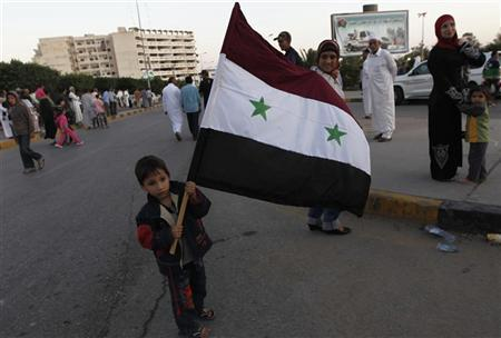 A boy holds a Syrian flag as a gesture of welcome during a military parade of anti-Gaddafi fighters coming back from Sirte, in Misrata October 28, 2011. REUTERS/Thaier al-Sudani