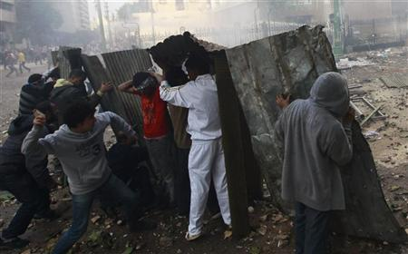 Protesters throw stones at army soldiers as they take cover at the cabinet near Tahrir Square in Cairo December 16, 2011. REUTERS/Amr Abdallah Dalsh