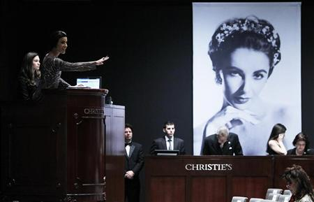 Christie's auctioneer Andrea Fiuczynski conducts an auction of Elizabeth Taylor's jewelry, clothing, art and memorabilia, near an image of the late actress at Christie's auction house in New York, December 14, 2011.    REUTERS/Carlo Allegri