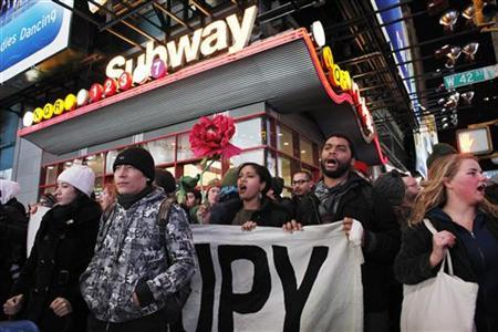 Protesters affiliated with the Occupy Wall Street movement hold a banner as they walk on the street during a protest in New York December 17, 2011.   REUTERS/Eduardo Munoz