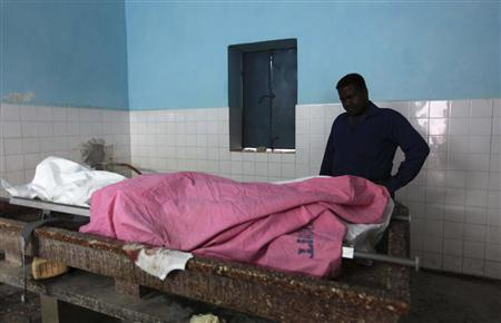 A Somali journalist looks at the dead body of his colleague Abdisalan Sheikh Hasan in southern Mogadishu, December 18, 2011. REUTERS/Feisal Omar