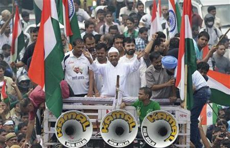 Anna Hazare (C, wearing white cap) waves from a vehicle after he leaves Tihar jail in New Delhi August 19, 2011. REUTERS/Adnan Abidi/Files
