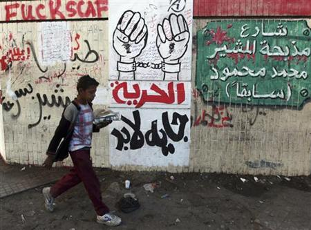 A boy walks past graffiti that reads ''Marshal massacres the street ''and ''Freedom will be coming'' during clashes with security forces in Cairo December 18, 2011. REUTERS/Amr Abdallah Dalsh