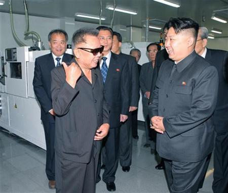 Kim Jong-il (front L) and his son Kim Jong-un (R) talk as they visit Mokran Video Company in Pyongyang in this undated picture released by the North's official KCNA news agency September 11, 2011. REUTERS/KCNA/Files