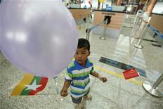 <p>A boy holds a Myanmar flag and a China flag (R) during the opening ceremony of Naypyitaw International Airport December 19, 2011. REUTERS/Soe Zeya Tun</p>