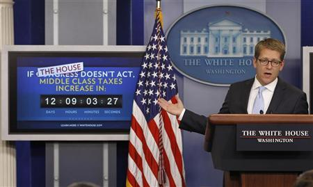 White House spokesman Jay Carney points to a payroll tax cut extension count down monitor in the briefing room of the White House in Washington December 19, 2011. House Speaker John Boehner effectively killed a short-term tax break and called on lawmakers to negotiate a full year payroll tax cut extension for 160 million U.S. workers. REUTERS/Jason Reed