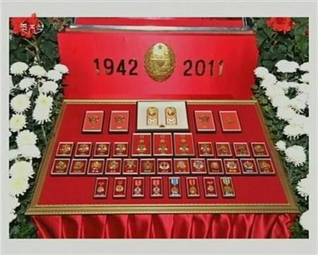 Medals belonging to former North Korean leader Kim Jong-il are displayed as he lies in state at the Kumsusan Memorial Palace in Pyongyang in this still picture taken from video footage of still images aired by KRT (Korean Central TV of the North) December 20, 2011. REUTERS/KRT via REUTERS TV