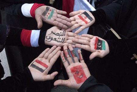 Women show the flags of Syria, Tunisia, Yemen, Egypt and Libya painted on their palms in the southern city of Taiz December 15, 2011. REUTERS/Mohamed al-Sayaghi