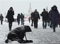 <p>A woman begs for money during heavy snowfall in central Moscow, December 21, 2010. REUTERS/Nikolay Korchekov</p>