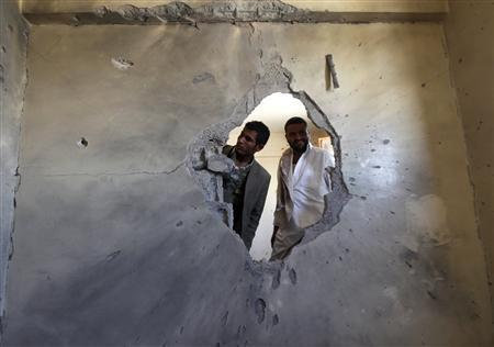 Followers of tribal leader Sadiq al-Ahmar look through a hole in a building damaged during recent clashes with government forces in Sanaa December 20, 2011.  REUTERS/Khaled Abdullah