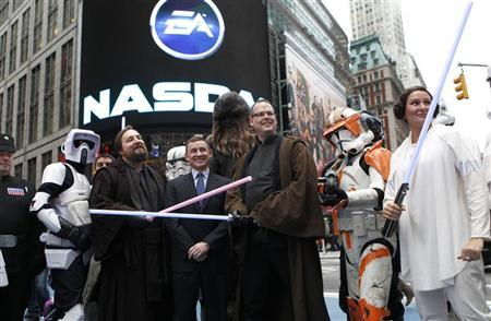 President of EA Labels Frank Gibeau (C), EA Senior Vice President Ray Muzyka (R) and EA Vice President Greg Zeschuk (L) stand with Star Wars characters outside the NASDAQ Market Site in New York's Times Square after ringing the opening bell for the trading day, December 20, 2011. REUTERS/Mike Segar