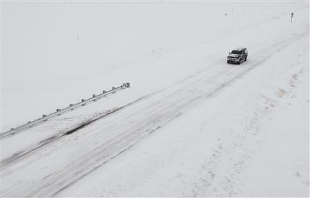 A truck travels along Highway 40 as snow covers the highway and the surrounding plains, west of Hays, Kansas December 20, 2011. REUTERS/Steven Hausler