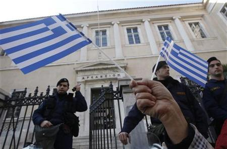 A protester holds Greek flags during a demonstration against a new property tax which has been included to the Greece's public power corporation's (PPC) bill to consumers in Athens December 2, 2011. REUTERS/John Kolesidis