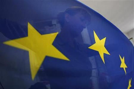 A seamstress sews a European Union (EU) flag in a small workshop in Belgrade October 13, 2011. REUTERS/Ivan Milutinovic/Files