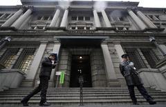 Человек идет мимо здания Банка Японии в Токио, 14 февраля 2011 г. Банк Японии в среду сохранил монетарную политику без изменений, но снизил оценку экономики второй месяц подряд, намекая, что готов предложить дополнительные денежные стимулы, если перспектива восстановления экономики окажется под угрозой. REUTERS/Toru Hanai