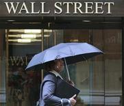 Женщина идет по Уолл-стрит в Нью-Йорке, 16 августа 2011 г. Акции США взлетели на 3 процента во вторник, так как инвесторы активно покупали бумаги банков, строительных и сетевых компаний, однако низкие объемы торгов, вероятно, усиливали все рыночные колебания. REUTERS/Brendan McDermid