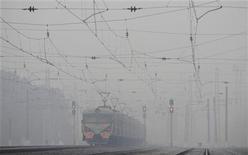 Поезд движется по путям в дымке у деревни Кустаревка в Рязанской области 9 августа 2010 года. Топ-менеджеры частного железнодорожного оператора Глобалтранс продадут ему 2,3 процента акций компании с дисконтом к рынку. REUTERS/Denis Sinyakov
