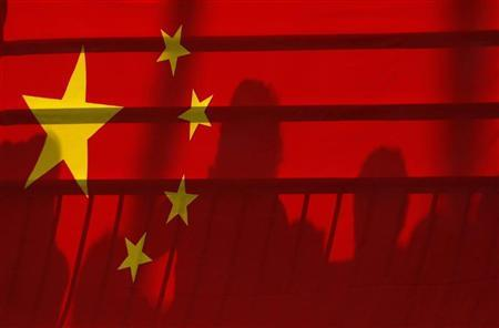 The shadows of spectators are seen through a Chinese national flag at the Beijing 2008 Olympic Games, August 12, 2008. REUTERS/Phil Noble