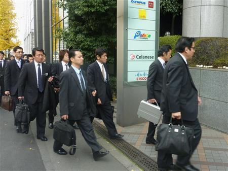 Investigators walk into an office building that houses three Olympus subsidiaries acquired under one of its loss-making schemes in Tokyo, December 21, 2011. REUTERS/Kyodo