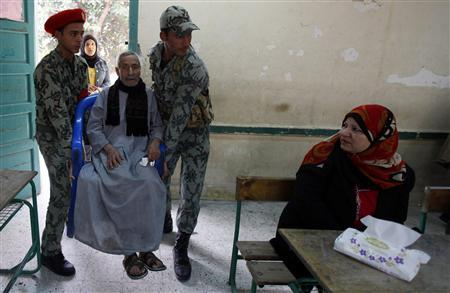 An elderly man is helped by army soldiers before casting his vote during the second round of parliamentary run-off elections at Imbaba in Giza, on the outskirts of Cairo December 21, 2011.   REUTERS/Mohamed Abd El-Ghany