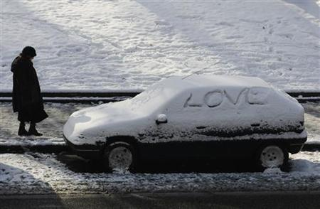A woman walks by a car covered in snow in Madrid January 11, 2010.  REUTERS/Susana Vera