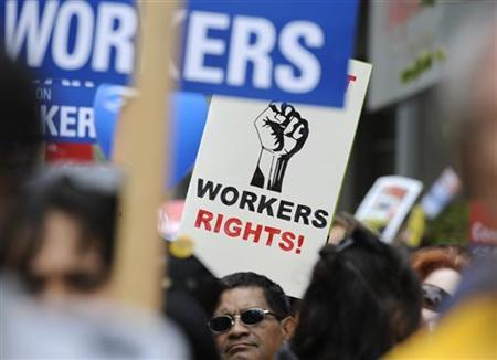 Participants carry signs during a march and rally by labor union supporters in Los Angeles, March 26, 2011. REUTERS/Phil McCarten