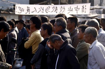 Residents of the village of Wukan in Lufeng county, Guangdong province listen to town representatives speak during a town meeting December 21, 2011. A protest march scheduled for Wednesday was called off after an agreement was reached between village representatives and government officials, seemingly ending the week-long stand-off. The villagers drove off officials and police, and held daily protests attracting thousands of residents outraged by the death in custody of local man Xue Jinbo.    REUTERS/David Gray