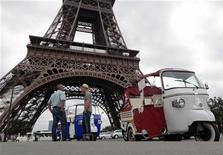 Водители моторикш ожидают пассажиров возле Эйфелевой башни в Париже 18 августа 2011 года. У жителей Парижа появился новый, доступный способ путешествовать по французской столице - бесплатные такси тук-тук. REUTERS/Charles Platiau