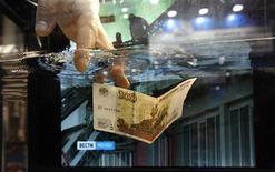 """Представитель компании 3M Co опускает сторублевую банкноту в контейнер с противопожарной жидкостью на международном форуме """"Охрана и безопасность"""" в Санкт-Петербурге 15 ноября 2011 года. Рубль подорожал в начале торгов четверга благодаря смещению баланса в сторону продавцов валюты. Исполняемые банками крупные клиентские заказы, а также закрытие валютных позиций перед Новым годом будут и далее оказывать основное влияние на котировки. REUTERS/Alexander Demianchuk"""