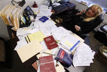 Consumer bankruptcy Attorney Linda Tirelli sits at her desk surrounded by allegedly falsified mortgage documents from civil cases that she is handling, in her office in White Plains, New York, December 14, 2011.  REUTERS/Mike Segar