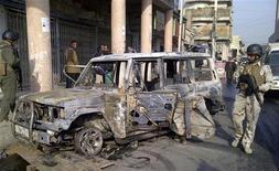 Солдат осматривает сгоревший автомобиль после взрыва в центре Багдада 22 декабря 2011 года. Как минимум 57 человек погибло в Багдаде в четверг в серии взрывов, первом крупном акте насилия в столице Ирака после вывода американских войск. REUTERS/Saad Shalash