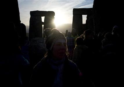 Revellers watch as the sun rises at Stonehenge on Salisbury plain in southern England December 22, 2011.  REUTERS/Kieran Doherty