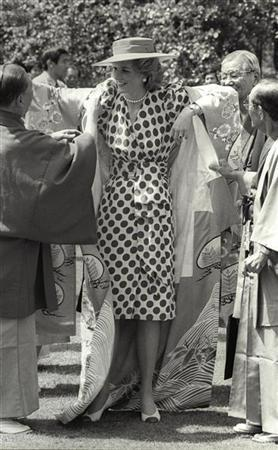 Kyoto city officials help Princess Diana as she puts on a Japanese Kimono during her tour of Nijo Castle on May 9, 1986 in Kyoto, Japan.  REUTERS/Shunsuke Akatsuka
