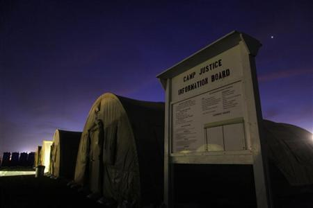 In this photo, reviewed by the U.S. military, an information board stands posted near a row of tented sleeping quarters before dawn at Camp Justice, the site of the U.S. war crimes tribunal compound, at Guantanamo Bay U.S. Naval Base, Cuba, July 15, 2009. REUTERS/Brennan Linsley/Pool