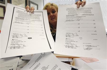Consumer bankruptcy attorney Linda Tirelli holds up mortgage documents from one of the civil cases she is handling in her White Plains, New York office, December 14, 2011.   REUTERS/Mike Segar