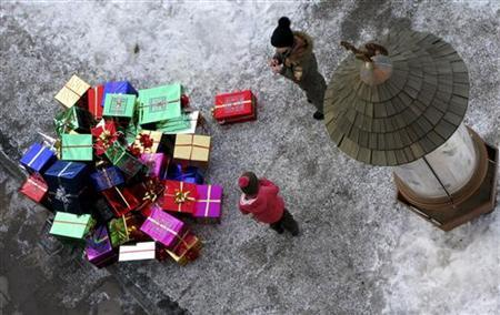 Children look at wrapped gifts on the ground as a man dressed as Santa Claus (not pictured) climbs a building to hang them during a ceremony in the northern Italian ski resort of Selva Di Val Gardena December 8, 2007.   REUTERS/Alessandro Bianchi