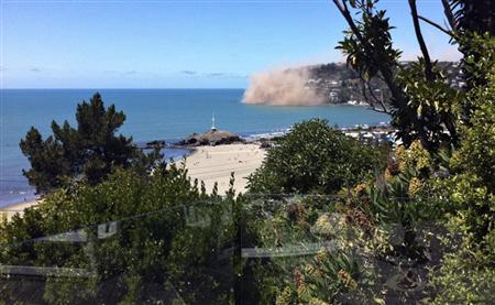 Dust rises from rocks were falling from a cliff in the Christchurch suburb of Sumner moments after an earthquake struck December 23, 2011.    REUTERS/Christine Brooks