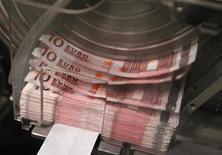Автомат пересчитывает купюры валюты евро в бельгийском Центробанке ы Брюсселе 8 декабря 2011 года. Евро вырос к доллару в пятницу, но все же может закончить год небольшим снижением, так как европейский долговой кризис, судя по всему, продлится еще много месяцев. REUTERS/Yves Herman