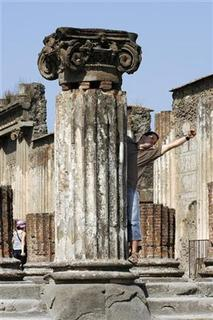 A tourist climbs on a column in Pompeii, the famous city next to Naples which was destroyed in AD 79 by the eruption of Mount Vesuvius, July 17, 2008. REUTERS/Giampiero Sposito