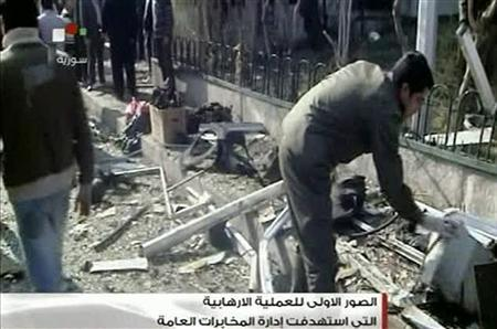 A man clears debris at a damaged building after a car bomb attack in Damascus, December 23, 2011. REUTERS/Syria Tv via Reuters Tv