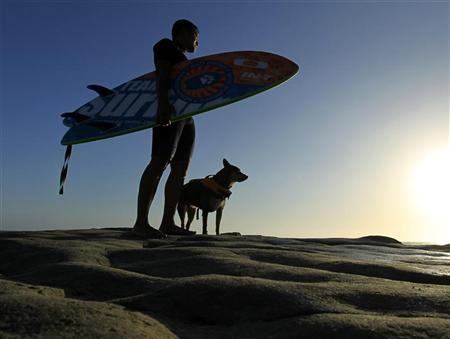 Surfdog Abbie and owner Michael Uy  look out at the ocean as they head home after a training session at dog beach in Del Mar, California May 13, 2010.  REUTERS/Mike Blake