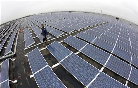 A worker walks in between solar panels on the roof of the Palexpo Exhibition Center in Geneva October 11, 2011. REUTERS/Denis Balibouse